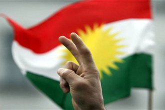 A protester make a victory sign with his hand in front of a Kurdish flag during a demonstration in Berlin